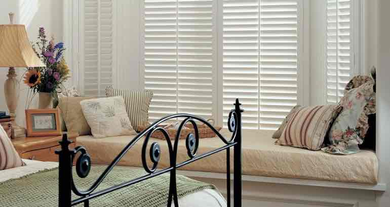 Plantation shutters in a modern bedroom bay window.