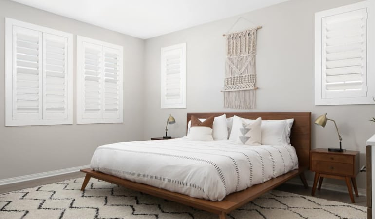 Plantation shutters in a model home bedroom.