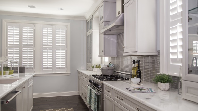 White shutters in Houston kitchen with modern appliances.