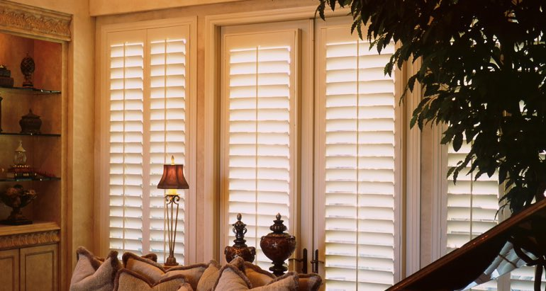 Plantation shutters on windows and door in Houston lounge