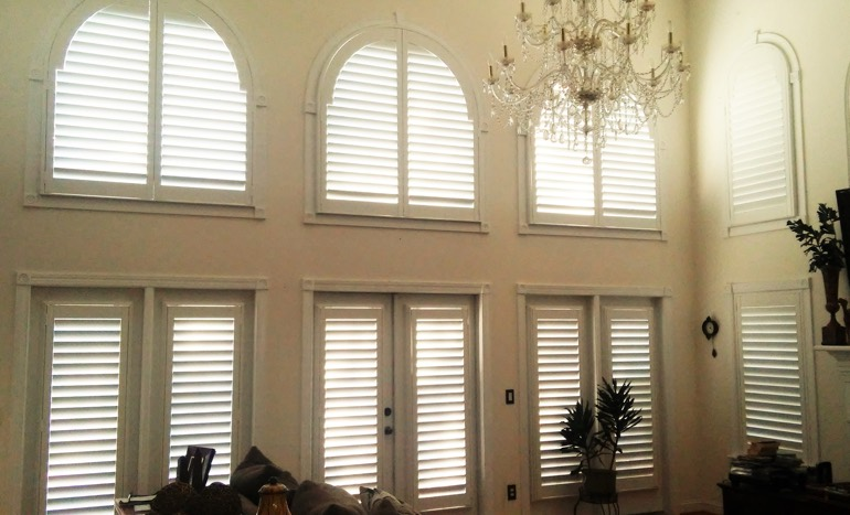 Television room in open concept Houston home with plantation shutters on arch windows.