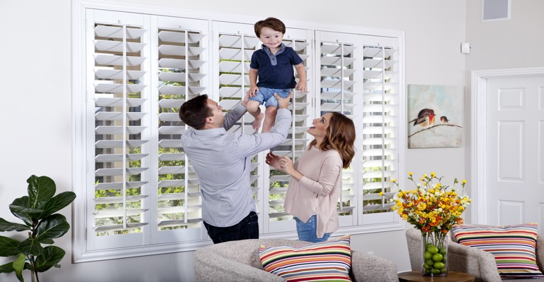 Parents Lifting Child In Front of Window Treatments