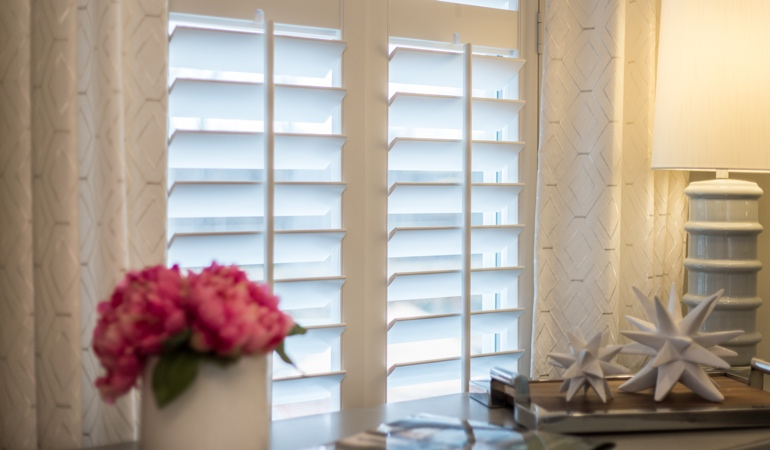Plantation shutters by flowers in Houston
