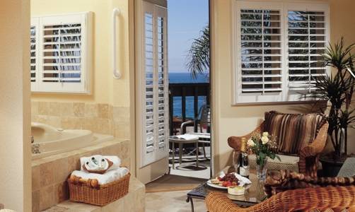 Plantation shutters on casement windows in a oceanfront home.