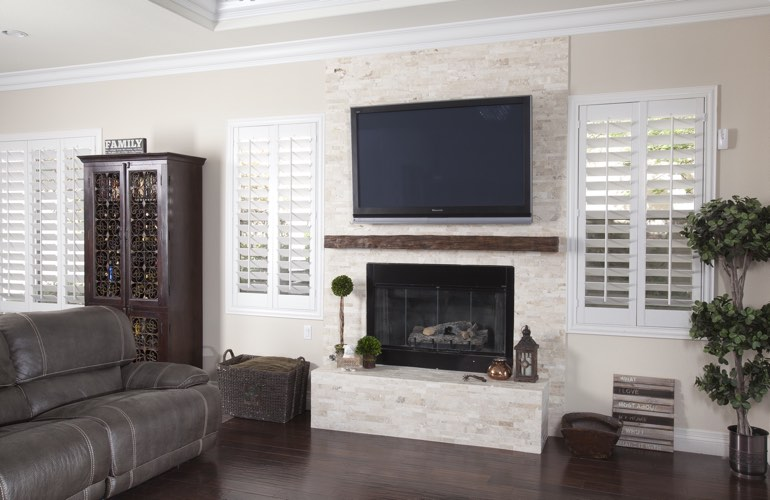 White plantation shutters in a Houston living room with plank hardwood floors.
