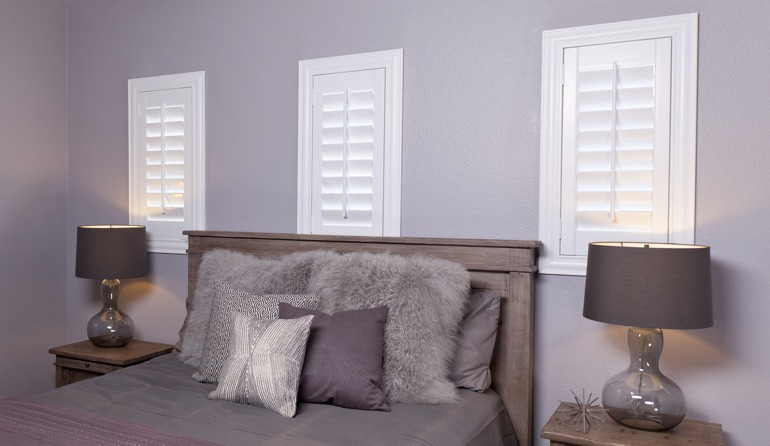 Classic plantation shutters in Houston bedroom windows.