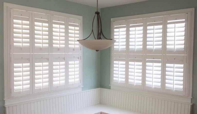 Pastel green wall in Houston kitchen with shutters.