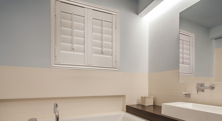 Studio waterproof shutters in Houston bathroom.