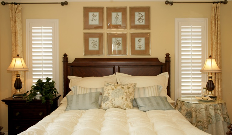 Bedroom with two tall plantation shutters on either side of bed in Houston