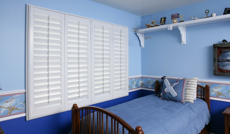 White plantation shutters in blue kids bedroom in Houston