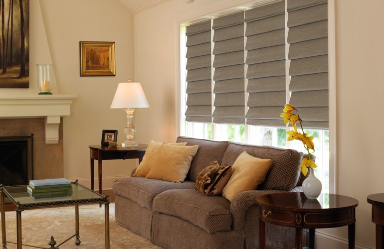 Living room with fireplace and tan Roman shades